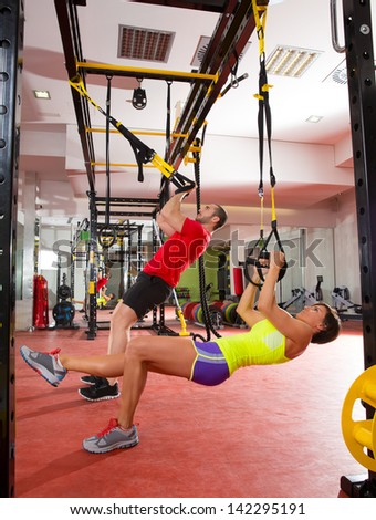 Crossfit fitness TRX training exercises at gym woman and man push-ups workout - stock photo