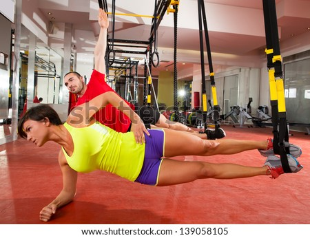Crossfit fitness TRX training exercises at gym woman and man side push-up workout - stock photo
