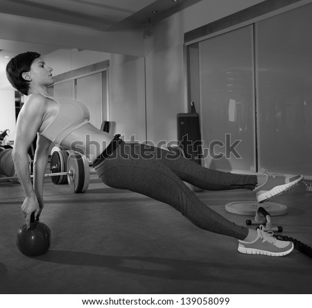 Crossfit fitness woman push ups with Kettlebell rear pushup exercise - stock photo