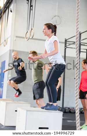 Crossfit group trains box jumps - stock photo