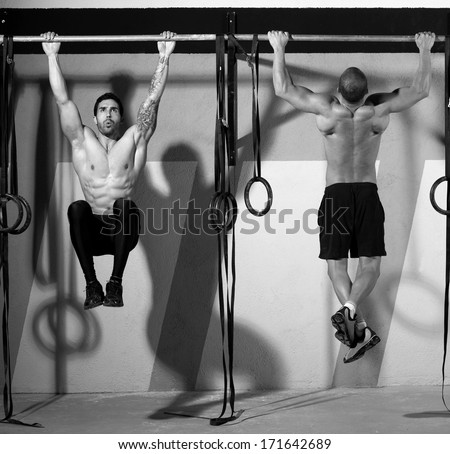 Crossfit toes to bar men pull-ups 2 bars workout exercise at gym - stock photo