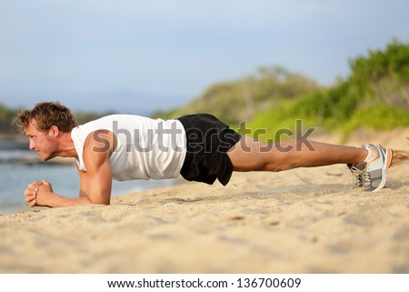 Crossfit training fitness man doing plank core exercise working out his midsection core muscles. Fit male fitness instructor planking exercising outside in summer on beach. - stock photo