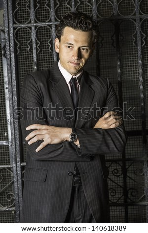 Crossing arms and biting lips a young businessman is seriously thinking outside a black metal gate./Deeply Thinking - stock photo