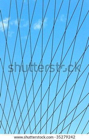 Crossing lines forming pattern against blue sky
