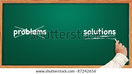 Crossing out problems and writing underline solutions on a blackboard - stock photo