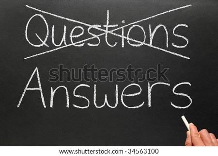 Crossing out questions and writing answers on a blackboard.