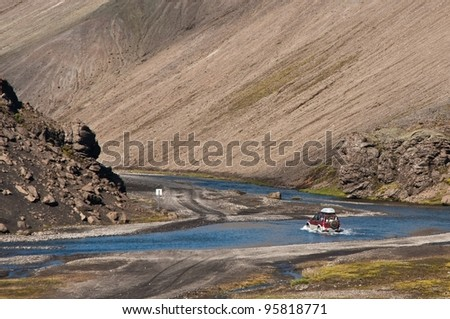 crossing the river with off road car - stock photo