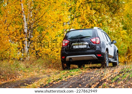 Crossover in front of autumn forest (rear view) - stock photo