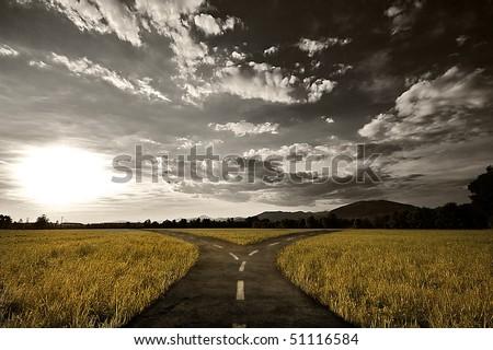 Crossroad in rural landscape under dusk sky - stock photo
