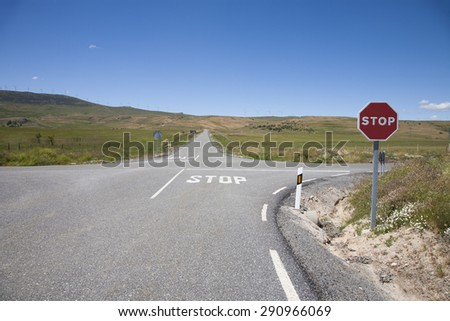 crossroad with stop symbol painted on asphalt and red hexagonal signal metal pole in rural road next to Madrid Spain Europe - stock photo