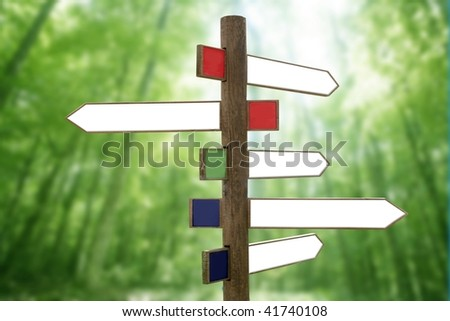 Crossroad wooden directional arrow signs copy space in green forest background [Photo Illustration] - stock photo