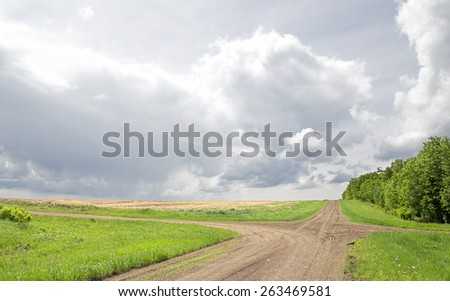 Crossroads dividing fields of farmland under heavy cloudy sky in rural landscape - stock photo