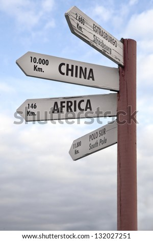 Crossroads Sign indicating the distance to China, Africa North Pole and Strasbourg. - stock photo