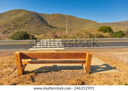 Crosswalk across road with a wooden bench - stock photo