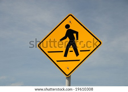 Crosswalk road sign against blue sky - stock photo