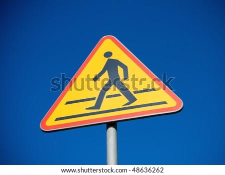 Crosswalk sign over blue sky - stock photo