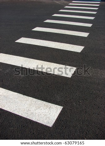 crosswalk stripes on black pavement forming abstract design - stock photo