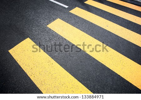 Crosswalk yellow lines on the road - stock photo