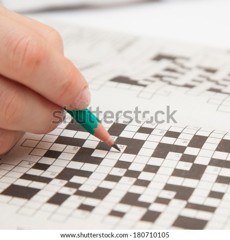 Crossword puzzle close-up.Hand doing crossword - stock photo