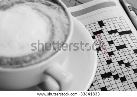 "crossword puzzle with ""business"" written in, and coffee"