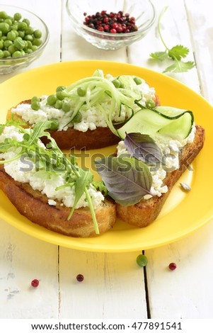 Crostini with cream cheese, green vegetables and herbs, vertical