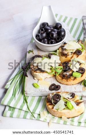 Crostini with fish with olives, cheese and chives