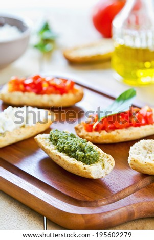 Crostini with Pesto, Cheese and Tomato by some ingredients - stock photo