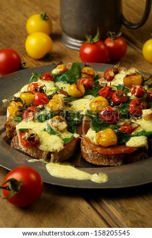 Crostini with prosciutto, swiss chard, cherry tomato vinaigrette, tin plate, rustic table - stock photo