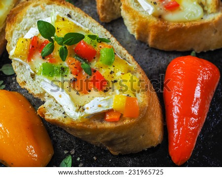 Crostini with roasted red and green pepper, goat cheese and oregano - stock photo