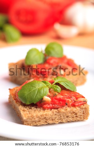 Crostini with rye bread, tomato, garlic and basil. National italian dish - stock photo