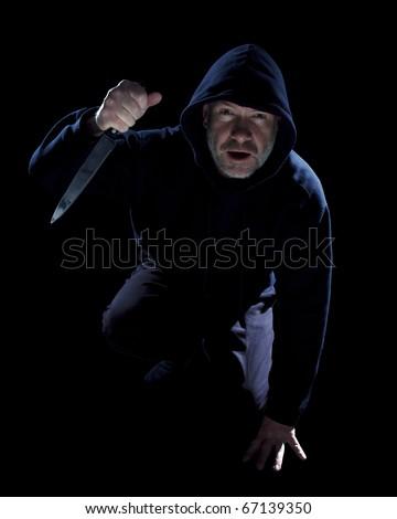 Crouching burglar with kitchen knife on black - stock photo