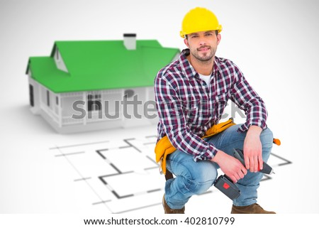 Crouching handyman holding power drill against blue house behind an architectural plan - stock photo