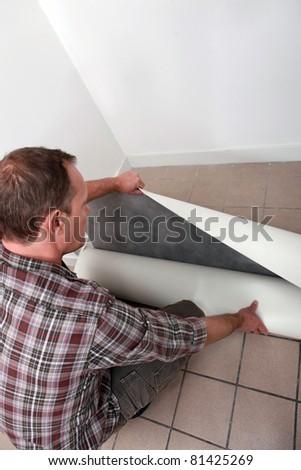 Crouching man unrolling flooring - stock photo