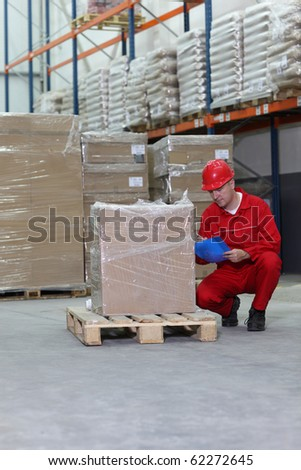 crouching worker checking inventory stocks at a factory storeroom. - stock photo