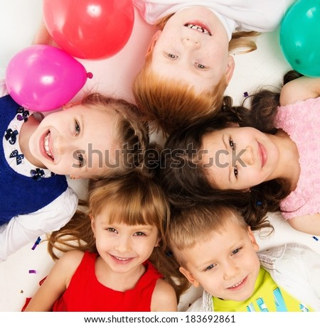 Croup of happy children lying in a circle  - stock photo