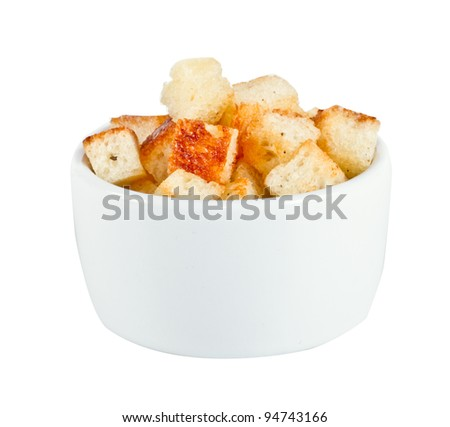 Crouton stack in a porcelain bowl and scattered isolated over white background. - stock photo