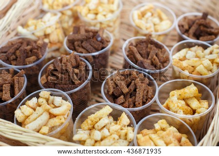 Croutons snack in plastic cups for party. Party snack lunch. Croutons crackers of white and brown whole grain bread. Many, plenty of beer snack. - stock photo