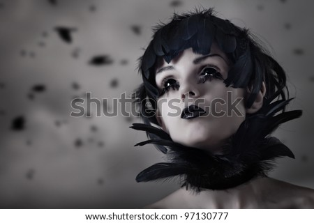 Crow girl with feather wig and black eyes, real contact lenses and makeup - stock photo