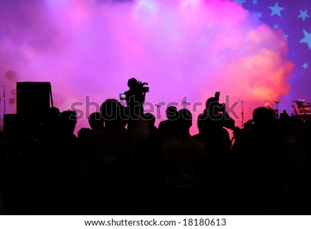 Crowd and cameraman wait for the performers to come on stage. Smoke signals their arrival - stock photo