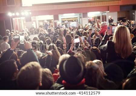 Crowd and fans taking photographs on mobile phones at a red carpet film premiere - stock photo
