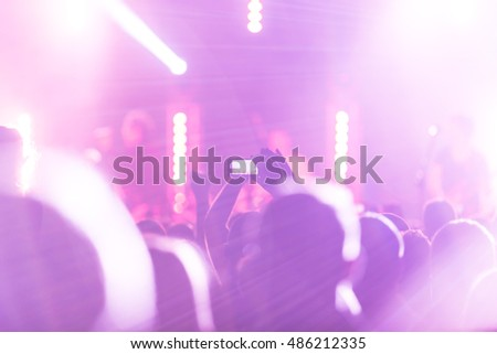Crowd at a concert. Fun with his hands up and smartphones.