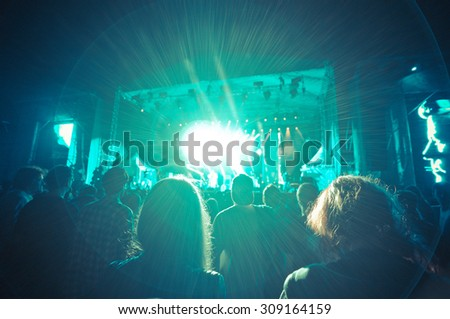 crowd at a concert in a blue light noise added - stock photo