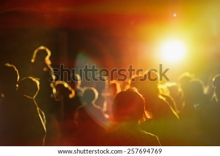 crowd at a concert in a red light noise added - stock photo