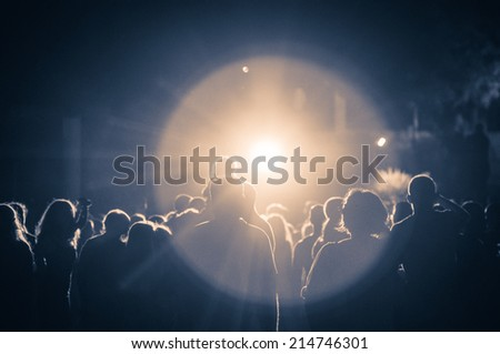 crowd at a concert in a vintage light. grain added - stock photo