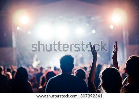 crowd at a concert in a vintage purple light noise added - stock photo