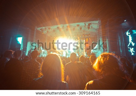 crowd at a concert in a wonderful light noise added - stock photo