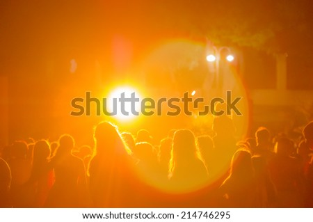 crowd at a concert in a yellow light - stock photo