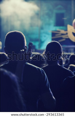 Crowd at concert - Cheering crowd in front of bright colorful stage lights - stock photo