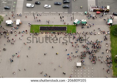 Crowd at the the base of Eiffel Tower in Paris. View of tiny people from landmark top. - stock photo