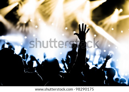 crowd cheering and hands raised at a live music concert - stock photo
